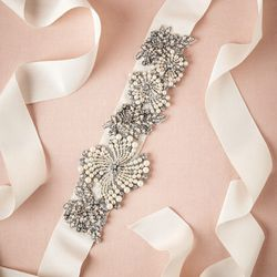 "<a href=""http://www.bhldn.com/shop-the-bride-bridal-accessories/roiled-crystal-sash/productoptionids/342632d7-5f2a-429b-89ef-5b539083fa5b"">Roiled Crystal Sash</a>, $180"