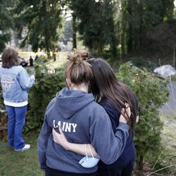 Eliana and her mother Jennifer Bakley hug while Melissa Phillips look over the smoldering remains of a house near Fredrickson, Wash., Sunday, Feb. 5, 2012, where, according to a sheriff's spokesman, three bodies were were found. The bodies are believed to be Josh Powell and his two sons. The explosion occurred moments after a Child Protective Services worker brought the two boys to the home for a supervised visit. (AP Photo/John Froschauer)