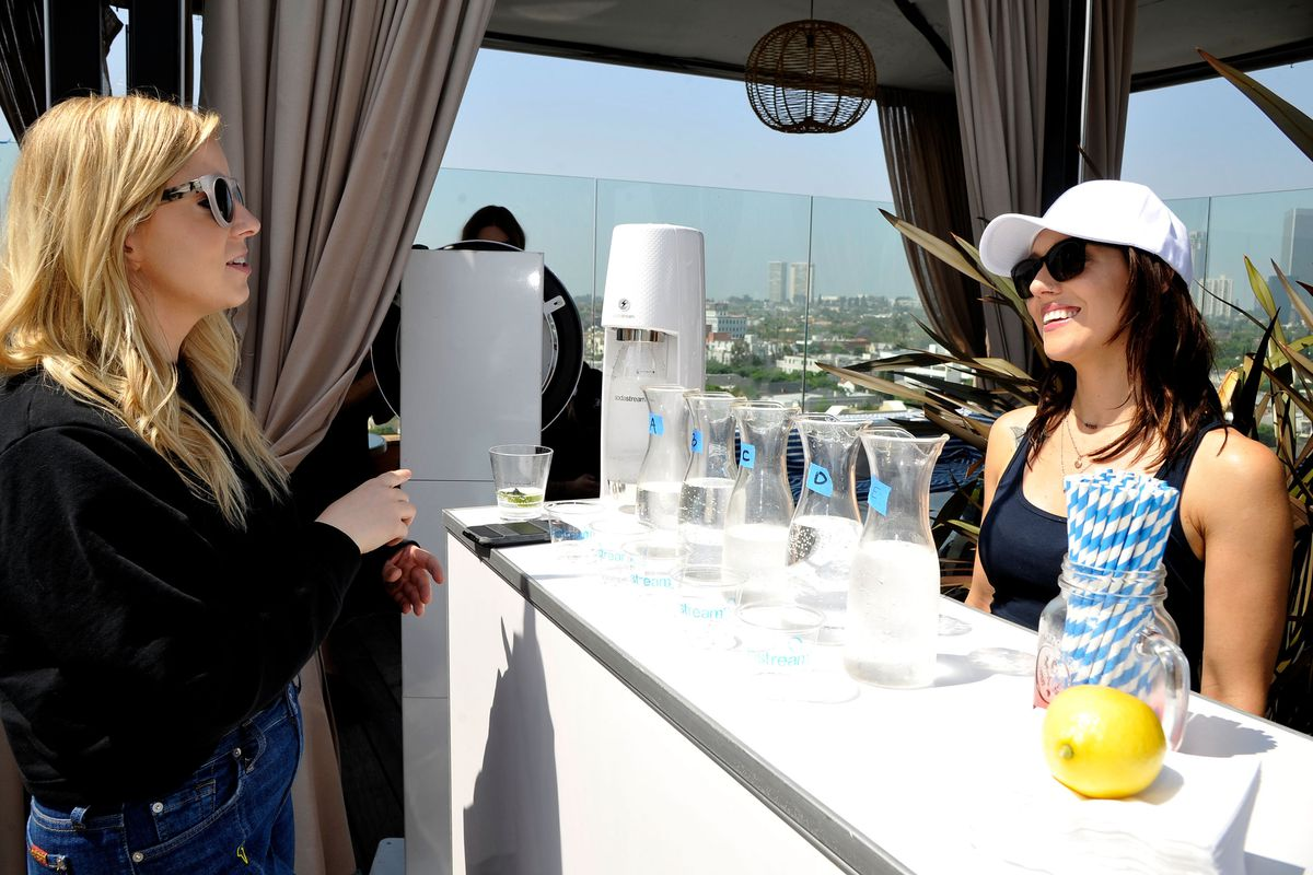 Two women participate in a blind taste test to see whether they can tell which soda water is which.