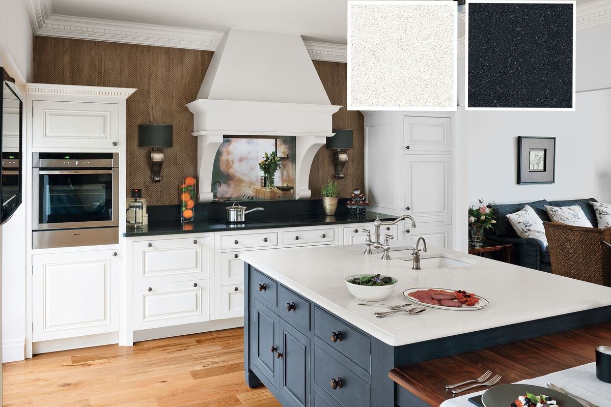 White quartz kitchen countertops with black cabinets used in an open plan room.