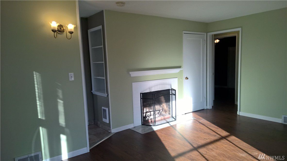A living room with hardwood floors, green walls, and a small fireplace