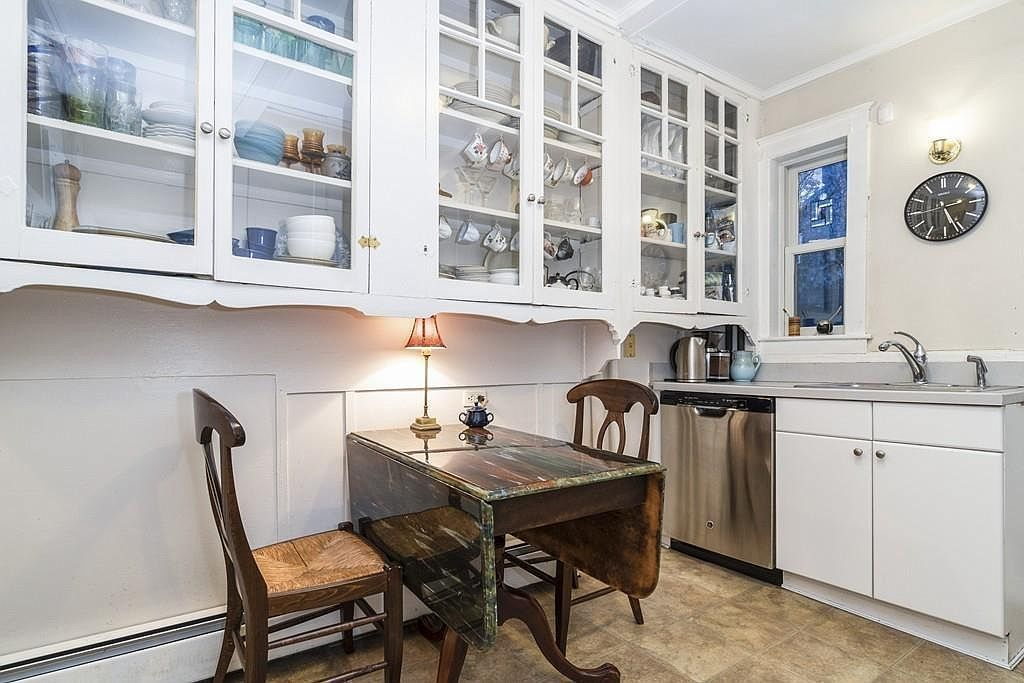 The sitting area of a kitchen, including a table and two chairs as well as glass cabinetry above.