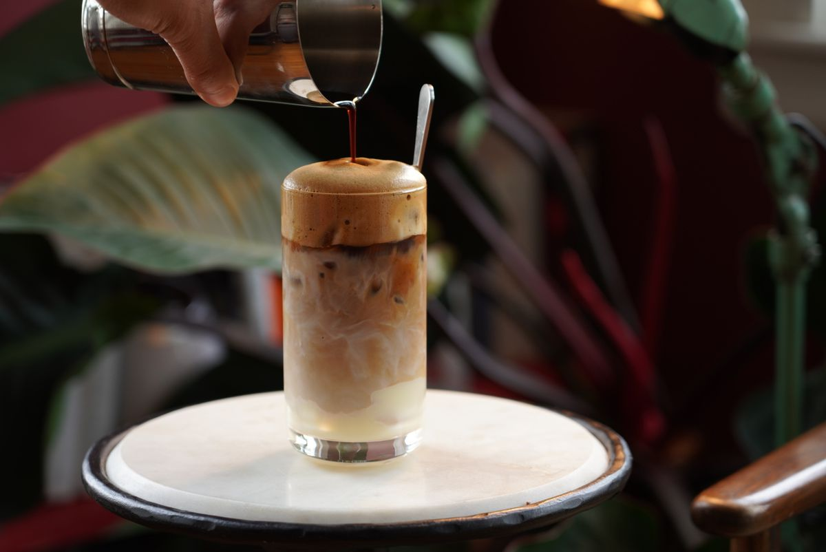 A hand pours liquid into a glass full of a foamy, milky iced coffee on a small white table. Plants are visible in the background.