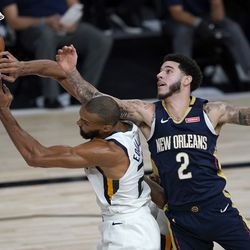Utah Jazz's Rudy Gobert, left, and New Orleans Pelicans' Lonzo Ball (2) reach for a loose ball during the second half of an NBA basketball game Thursday, July 30, 2020, in Lake Buena Vista, Fla. (AP Photo/Ashley Landis, Pool)
