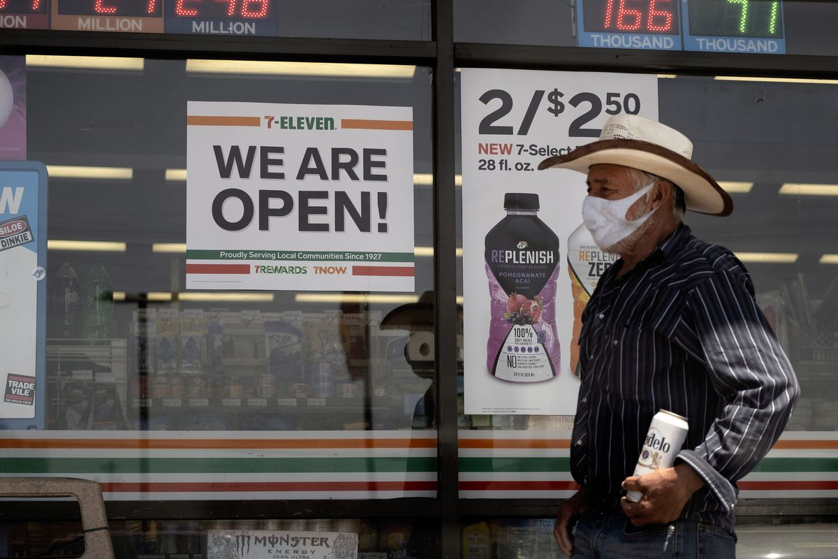 In this Sunday, May 10, 2020 photo a man wearing a protective mask from the coronavirus leaves a 7-Eleven store Los Angeles Calif. The most significant reopening of the California economy during the coronavirus pandemic started Friday with tens of thousands of businesses cleared to open with limitations.