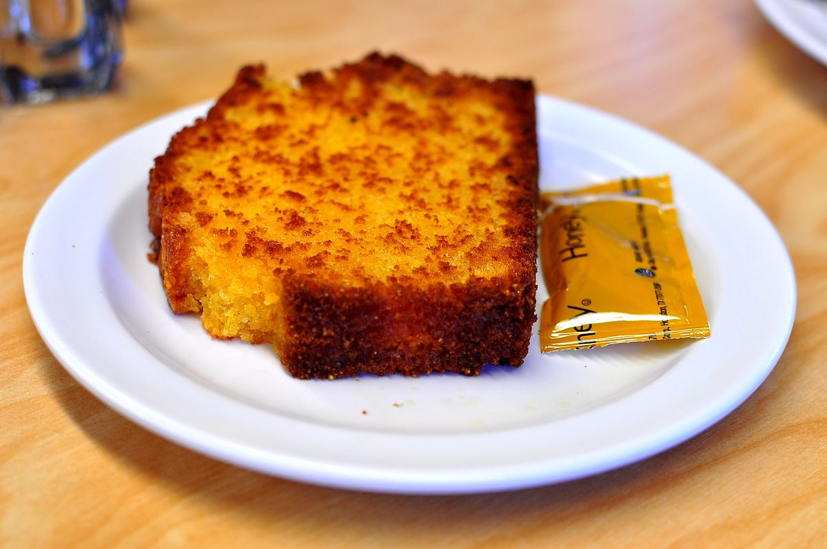 A white plate with a slice of toasted corn bread with a packet of honey on the side.