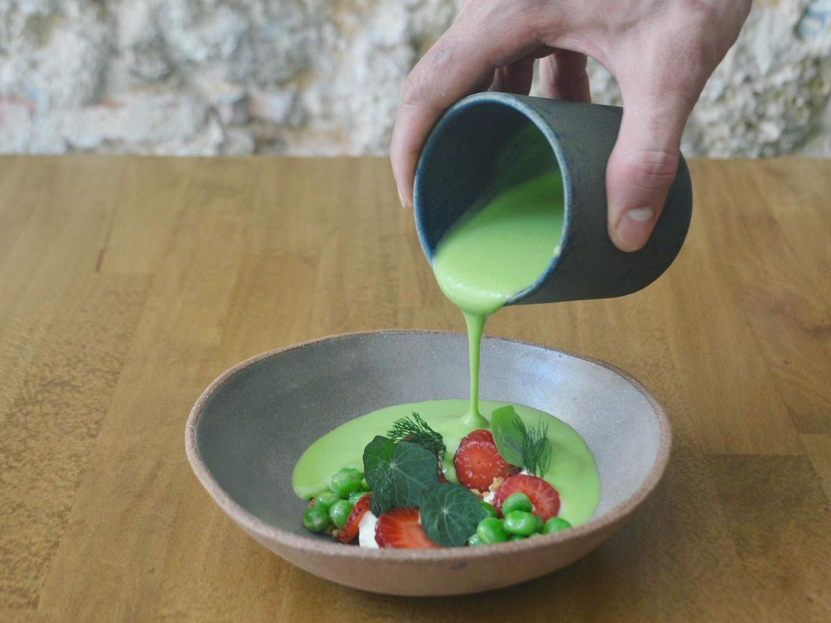 A server pours bright, thick pea soup from a ceramic cup into a ceramic bowl that already contains slices of pickled strawberries, walnuts and cashew cream
