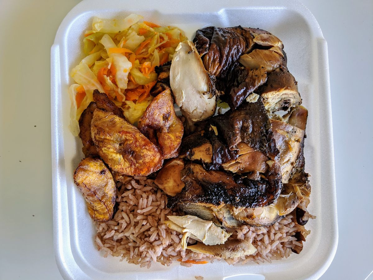 A styrofoam take-out container filled with chicken, plantains, rice, and a salad.