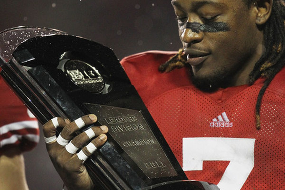 Aaron Henry admires the Leaders Division trophy after beating Penn State 45-7, but more important hardware will be on the line next Saturday against Michigan State.