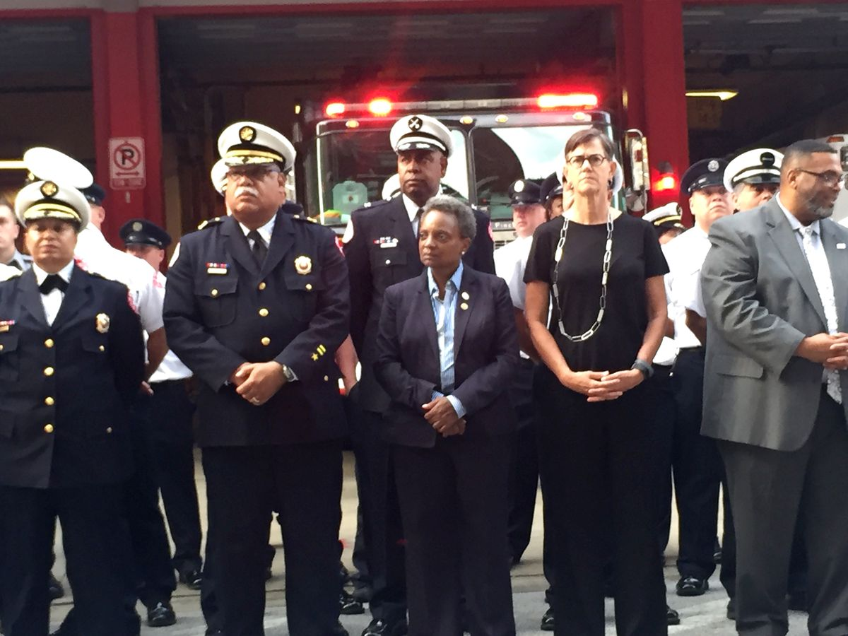 Mayor Lori Lightfoot and her wife, Amy Eshleman, take part in a 9/11 ceremony outside Chicago Fire Department Engine 42 firehouse