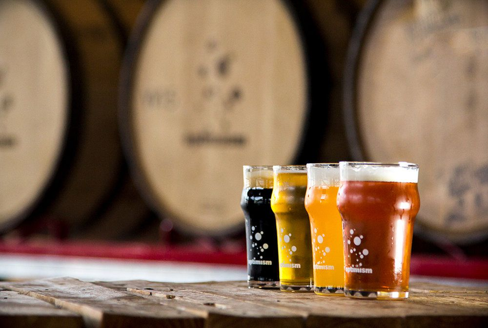 Beers of different colors from Optimism Brewing Company in front of barrels.