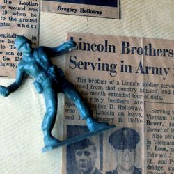 ADVANCE FOR USE SATURDAY, APRIL 21, 2012, AT 12:01 A.M. CDT AND THEREAFTER- This April 9, 2012, photo shows a toy Army figure on old newspaper articles about Gregory Holloway and his brother's deployment in the Vietnam War, in Bee, Neb. Holloway's mother, Inez Davis, kept two toy plastic soldiers atop her stereo in front of a couple of pictures of her two sons, Gregory and Stephen Holloway, who were away at war. Two days after a toy soldier fell to the floor in Nebraska, Gregory's wife at the time called his mother to say she had been told he was missing after he was injured by a granade explosion.