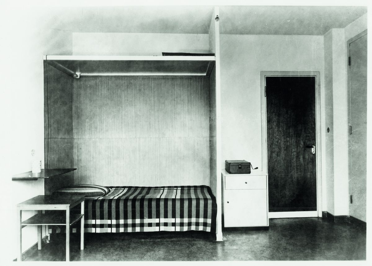 A vintage photograph of a Bauhaus dorm room. In the room is a bed that has a Prellerdecke blanket on it with intersecting lines.