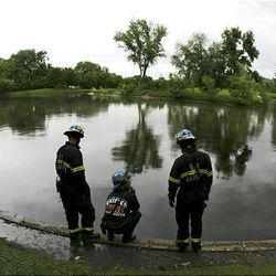 Firefighters from Unified Fire check the air for dangerous gases after oil from a broken Chevron pipeline leaked into the pond at Liberty Park on Saturday.