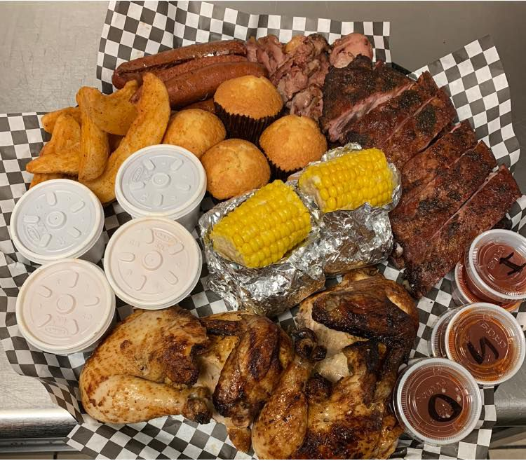A tray is laden with barbecue ribs, cornbread muffins, jo jo fries, smoked chicken, sauce containers and corn on the cob
