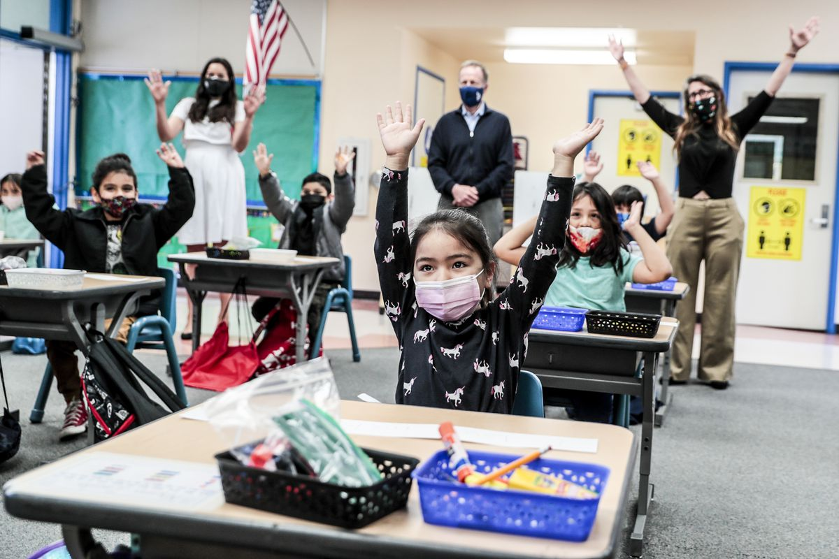 Young children wearing masks and sitting at separate desks participate in an activity that has them all raise their hands over their heads.