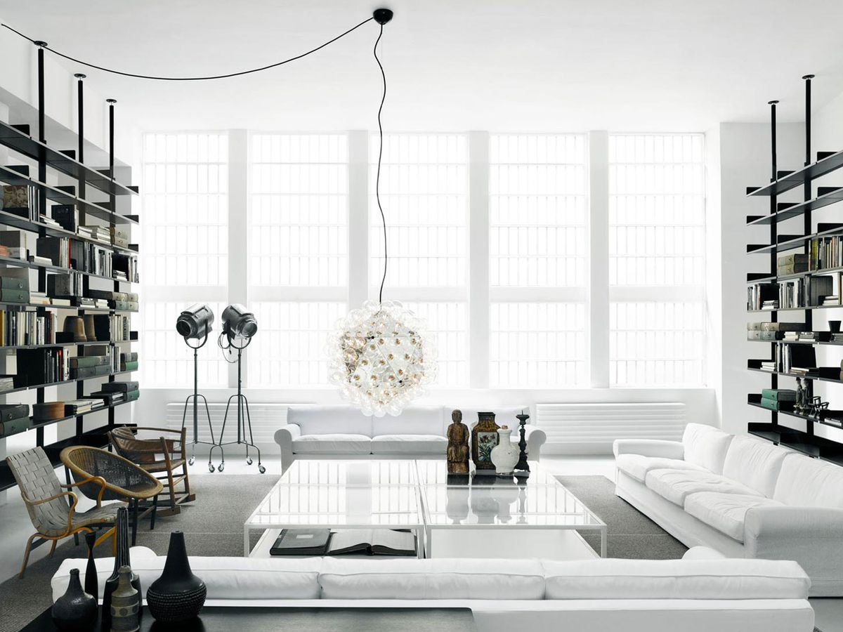 The interior of a furniture showroom in Milan, Italy. There are various items of design and furniture objects in a white room with tall windows letting in natural light.