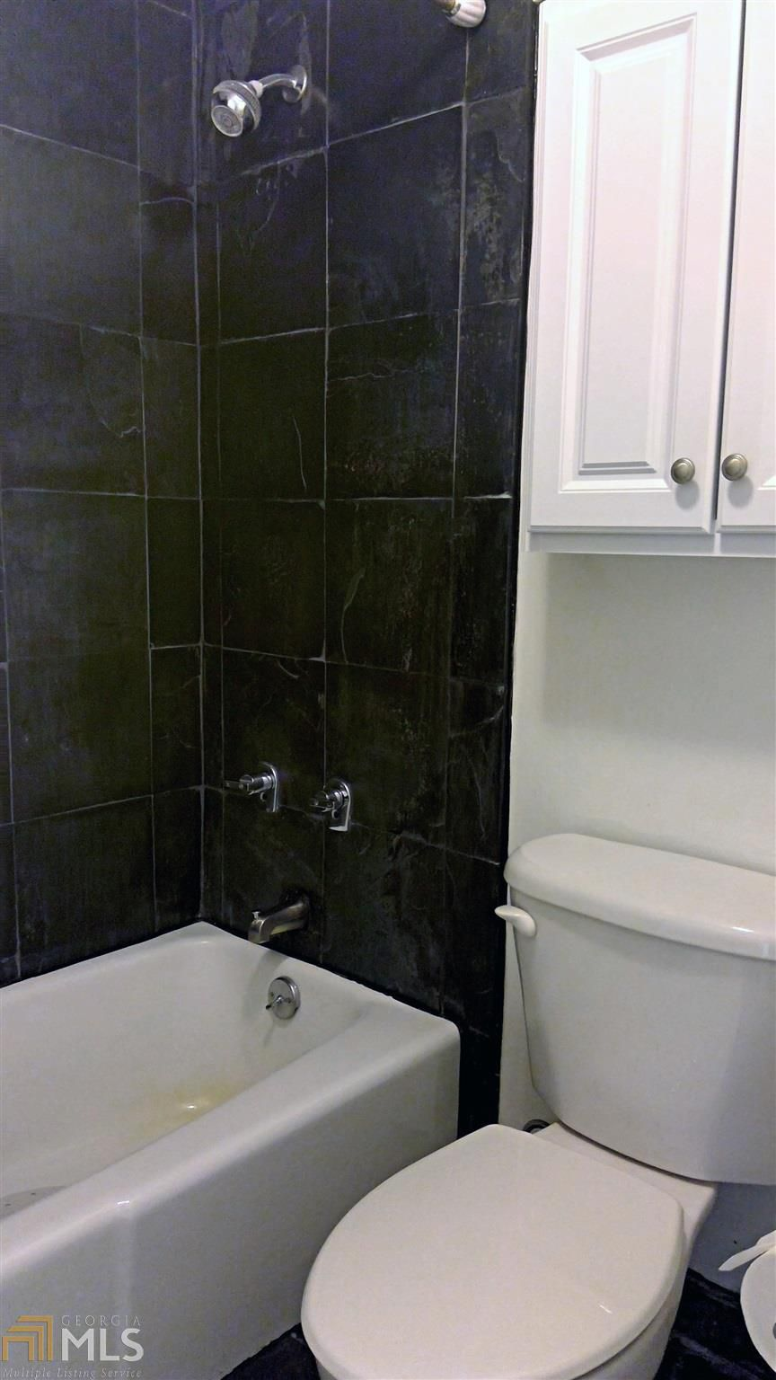 A shower with black tile and a white toilet at right.