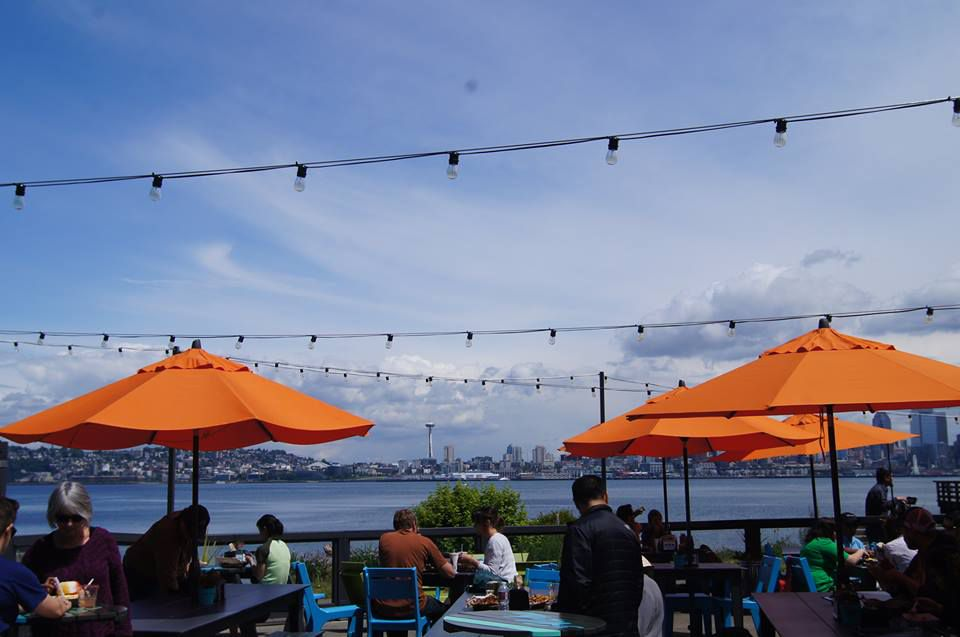 Marination Ma Kai's scenic patio overlooking Seattle with orange umbrellas and tables.