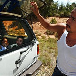 Esteban Cosillos, an illegal immigrant from Mexico, closes the hatch of the Ford Explorer he was driving on U.S. 191 near Blanding en route to Denver. The vehicle carried eight illegal immigrants looking for construction work and passed through southeastern Utah on Labor Day.