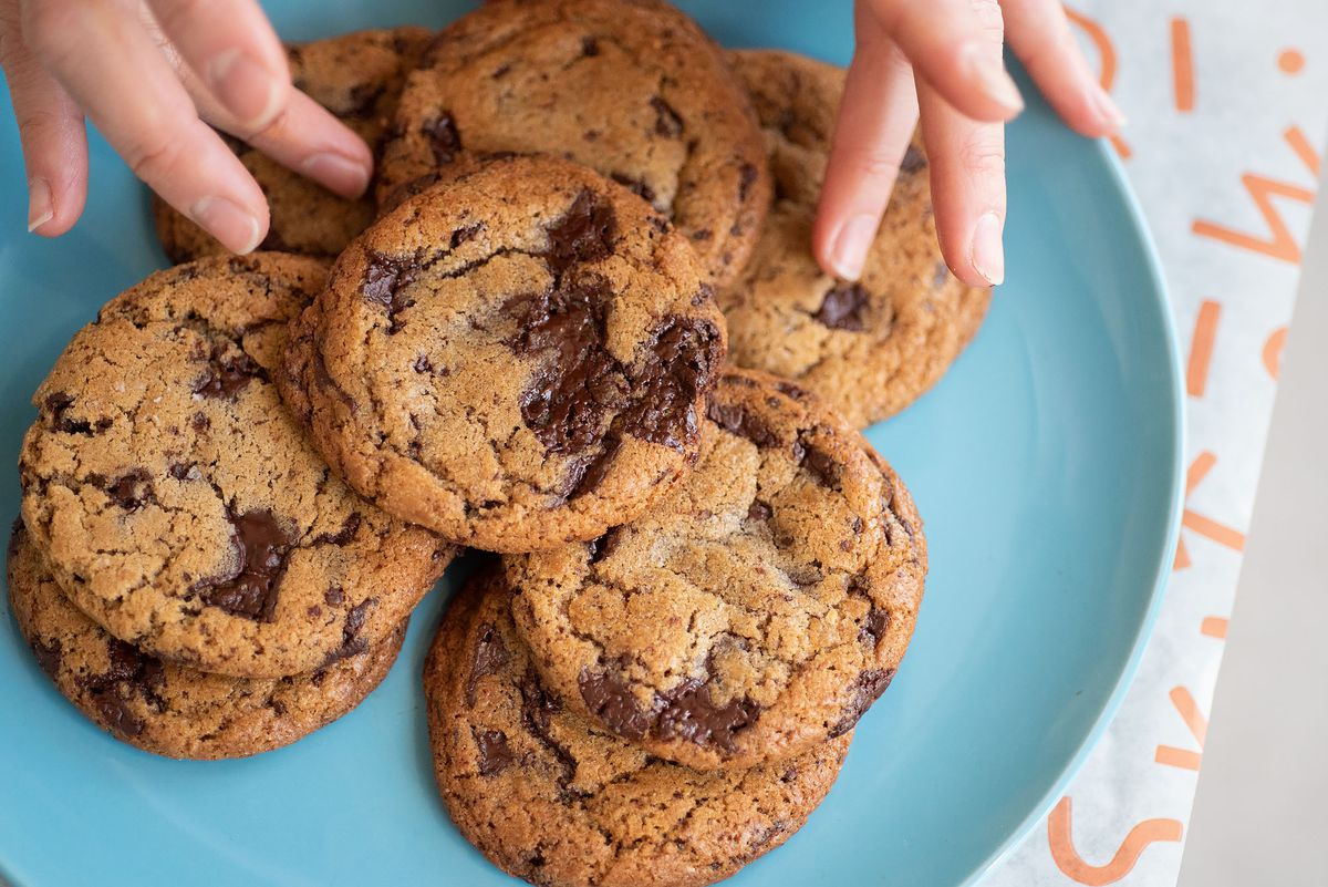 Two hands move around fresh chocolate chip cookies on a blue plate.
