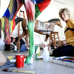 Wendy Dimick, right, McCall Takos, left, and Michael Collins, rear, work on painting fiberglass horses for Ogden Pioneer Days.