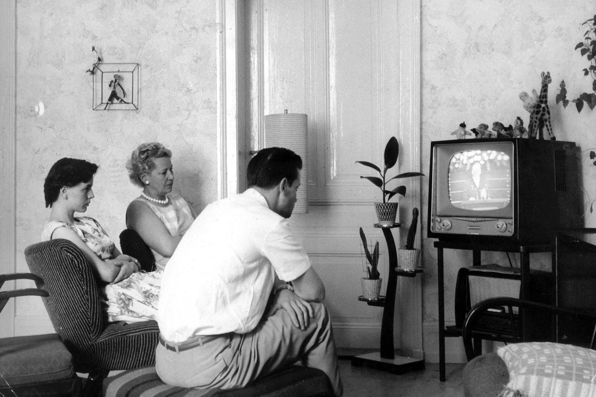 Family in front of television in 1960s