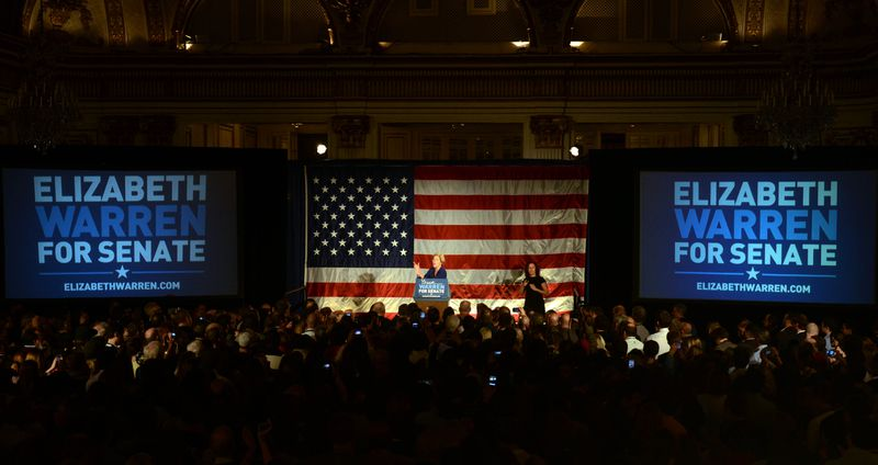 """A large crowd at a 2012 campaign event for Elizabeth Warren with her onstage in front of a large American flag and flanked by """"Elizabeth Warren for Senate"""" signs."""