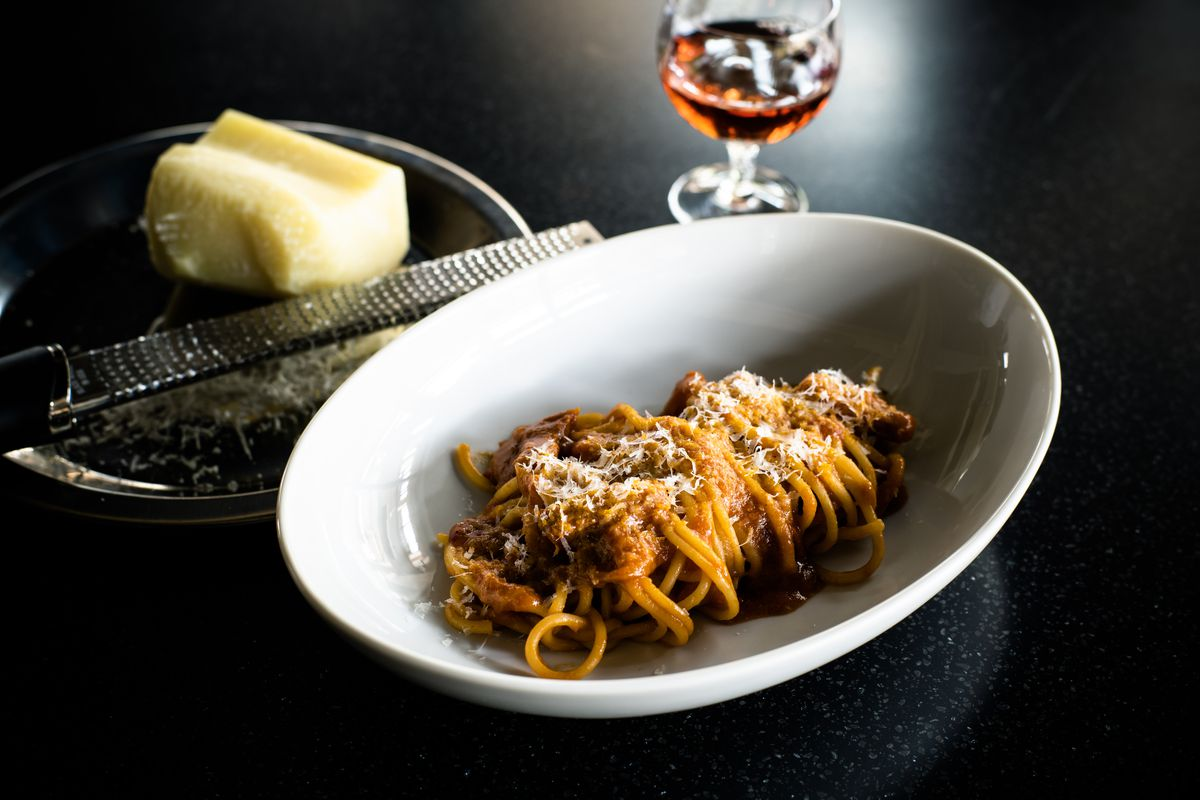 white place with spaghetti and red sauce next to glass of wine and cheese for grating