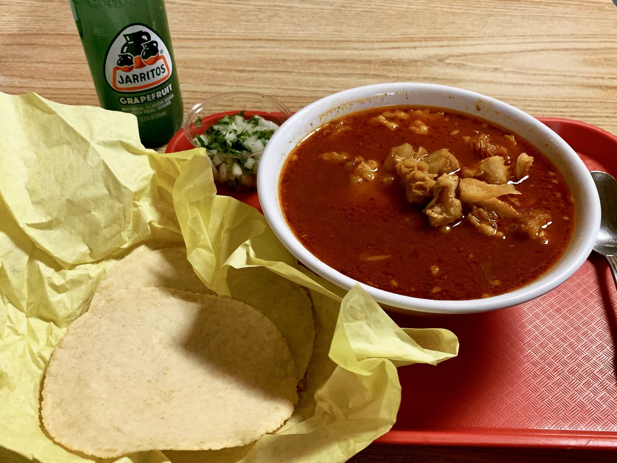 A picture of a red bowl of menudo with tortillas and a Jarritos at Santo Domingo Taqueria