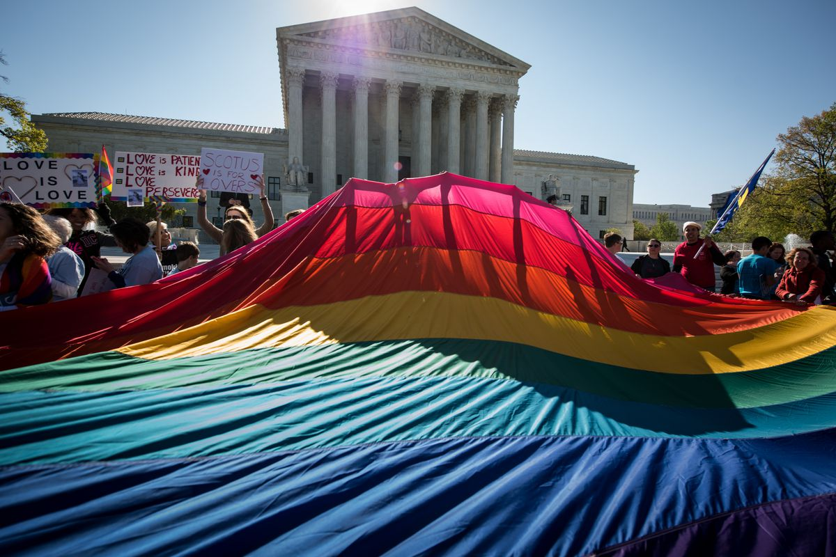 Demonstrators outside the Supreme Court building unfurl a gigantic rainbow flag.