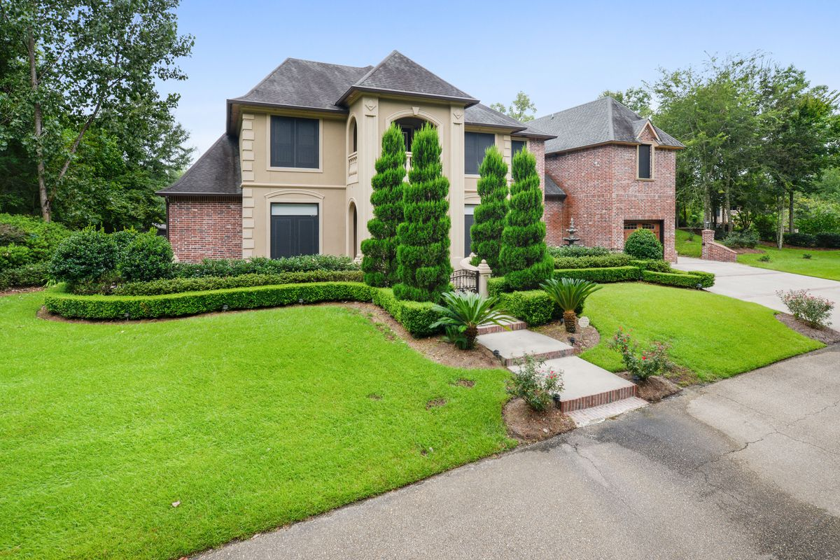 A two-story brick mansion is surrounded by topiaries and green grass.