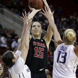 Utah's Michelle Plouffe (15) puts up a shot between Washington's Kelsey Plum, left, and Katie Collier in the second half of an NCAA college basketball game in the Pac-12 women's tournament Thursday, March 6, 2014, in Seattle. Plouffe led all scorers with 30 points and Utah won 65-53. (AP Photo/Elaine Thompson)