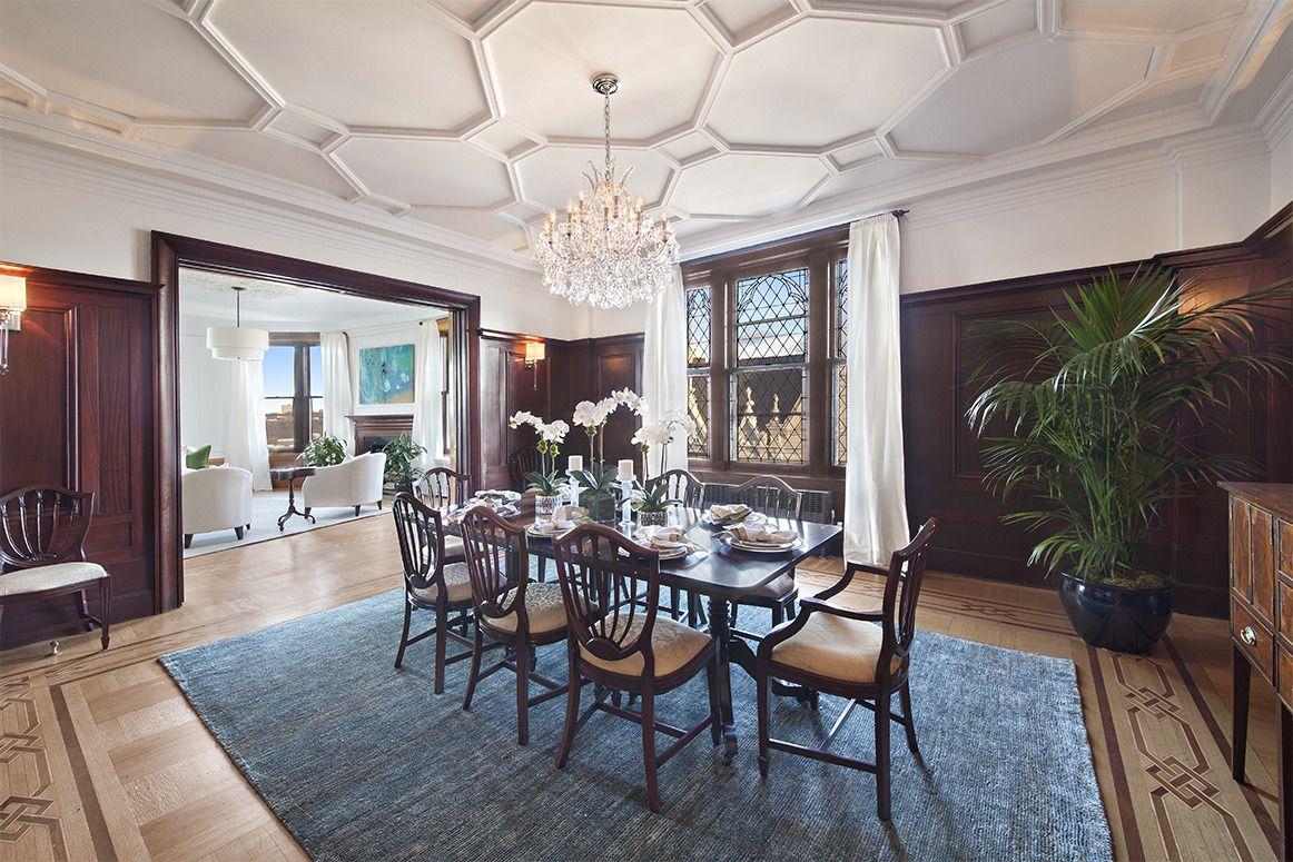A spacious dining room with octagonal pattern in the ceilings, dark wood paneling on walls, and a 8-person dining setup.