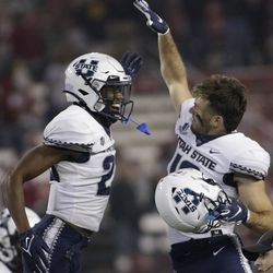 Utah State safety Dominic Tatum, left, and wide receiver Brandon Bowling celebrate the team's 26-23 win against Washington State in an NCAA college football game, Saturday, Sept. 4, 2021, in Pullman, Wash.