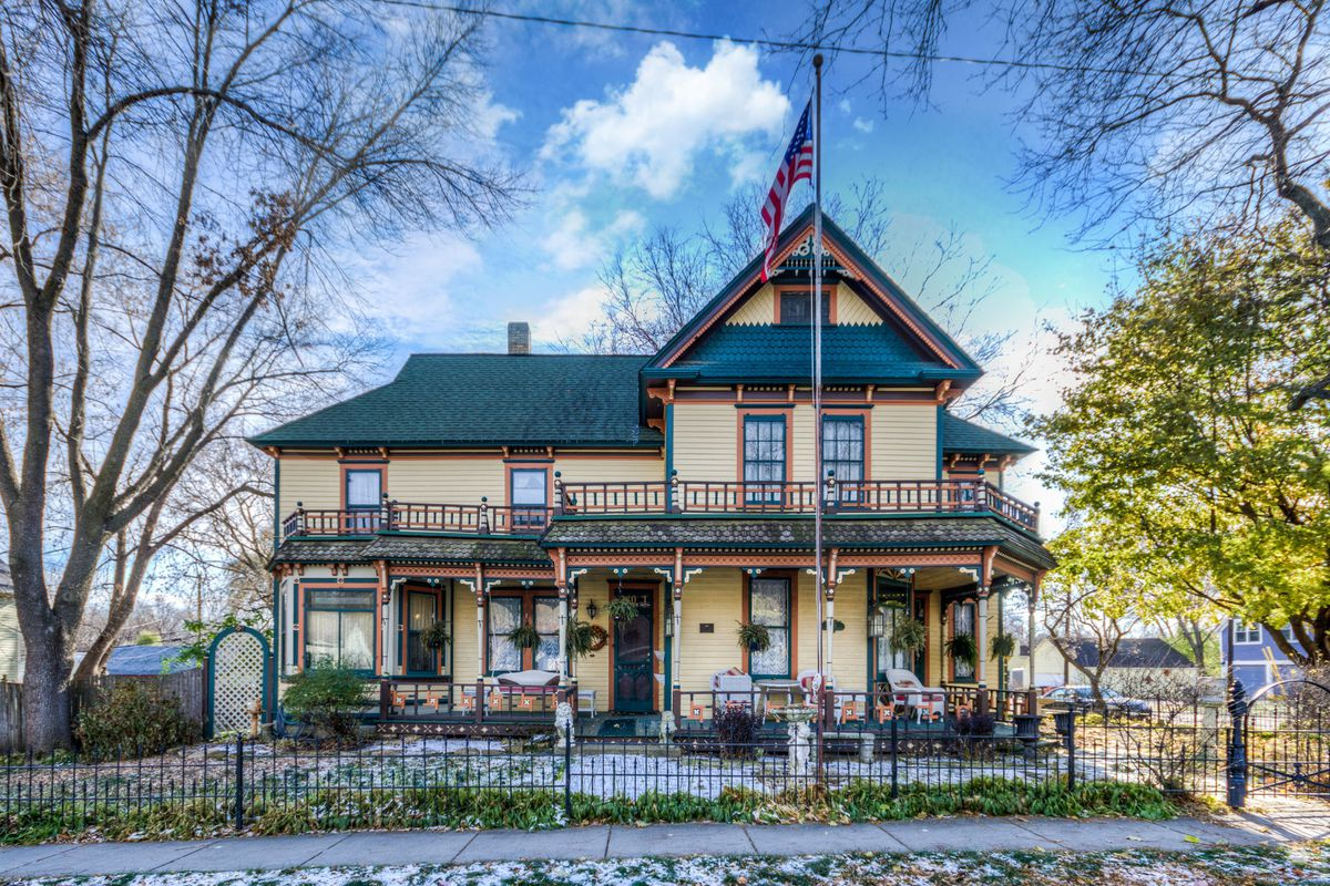 A beige, green, and coral Victorian house with a large front porch and an iron fence in front of it.