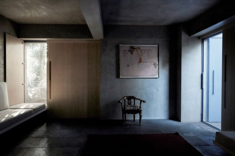 A dimly lit living room with concrete floors. Light streams in from a door on the right side, while a white built-in sofa sits on the left.