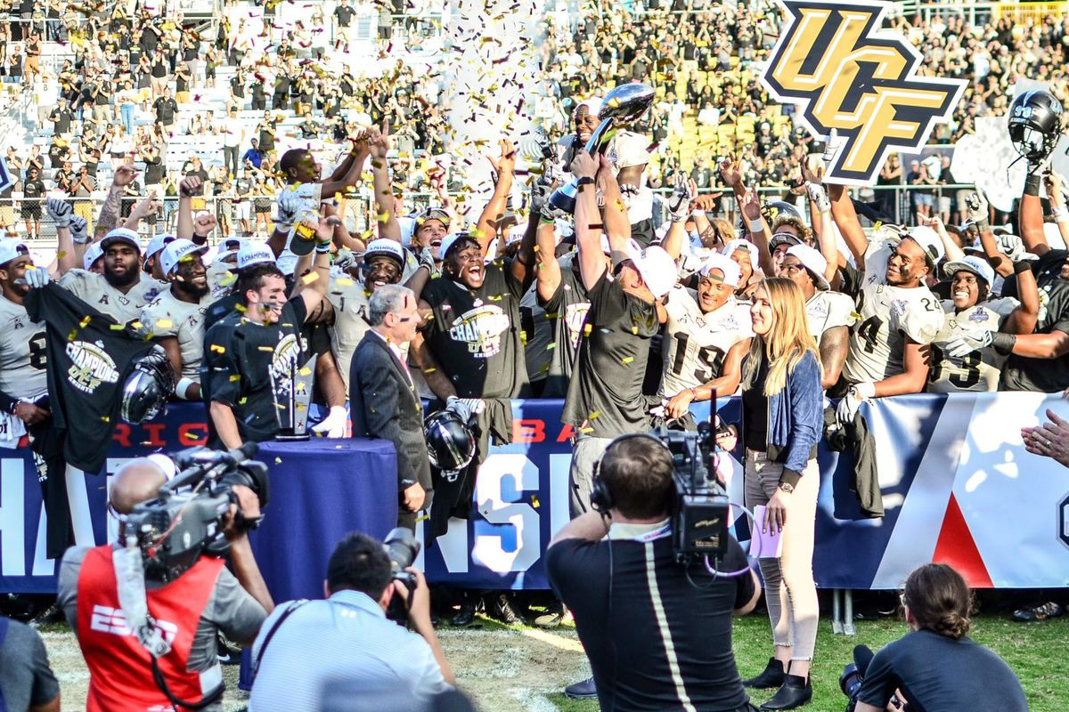 UCF head coach Scott Frost holds up the American Athletic Conference Championship Trophy as his team celebrates winning the title Saturday, December 2, 2017. (Photo: Derek Warden)