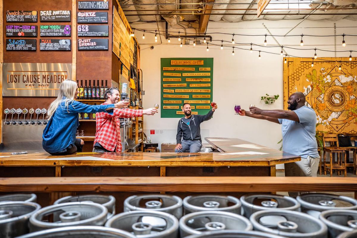 Founders of Rollin Roots and Serpentine Cider share a toast in their tasting room