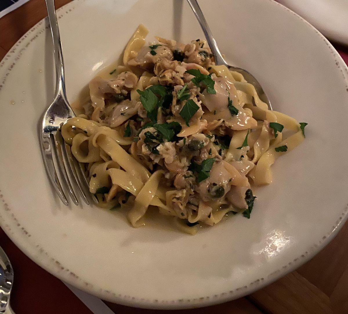 Tagliatelle pasta sits in a bowl with clams, bright green parsley, and butter
