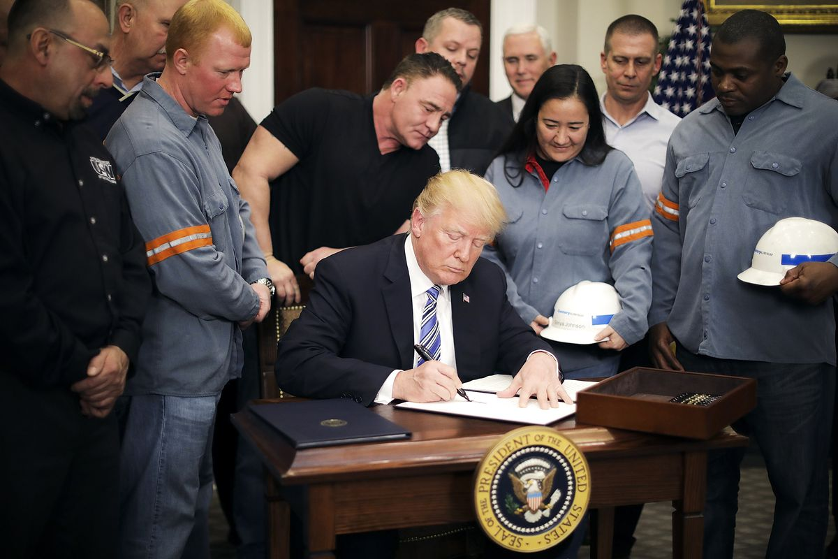 Surrounded by steel and aluminum workers, President Trump signs a 'Section 232 Proclamation' on steel imports on March 8, 2018.