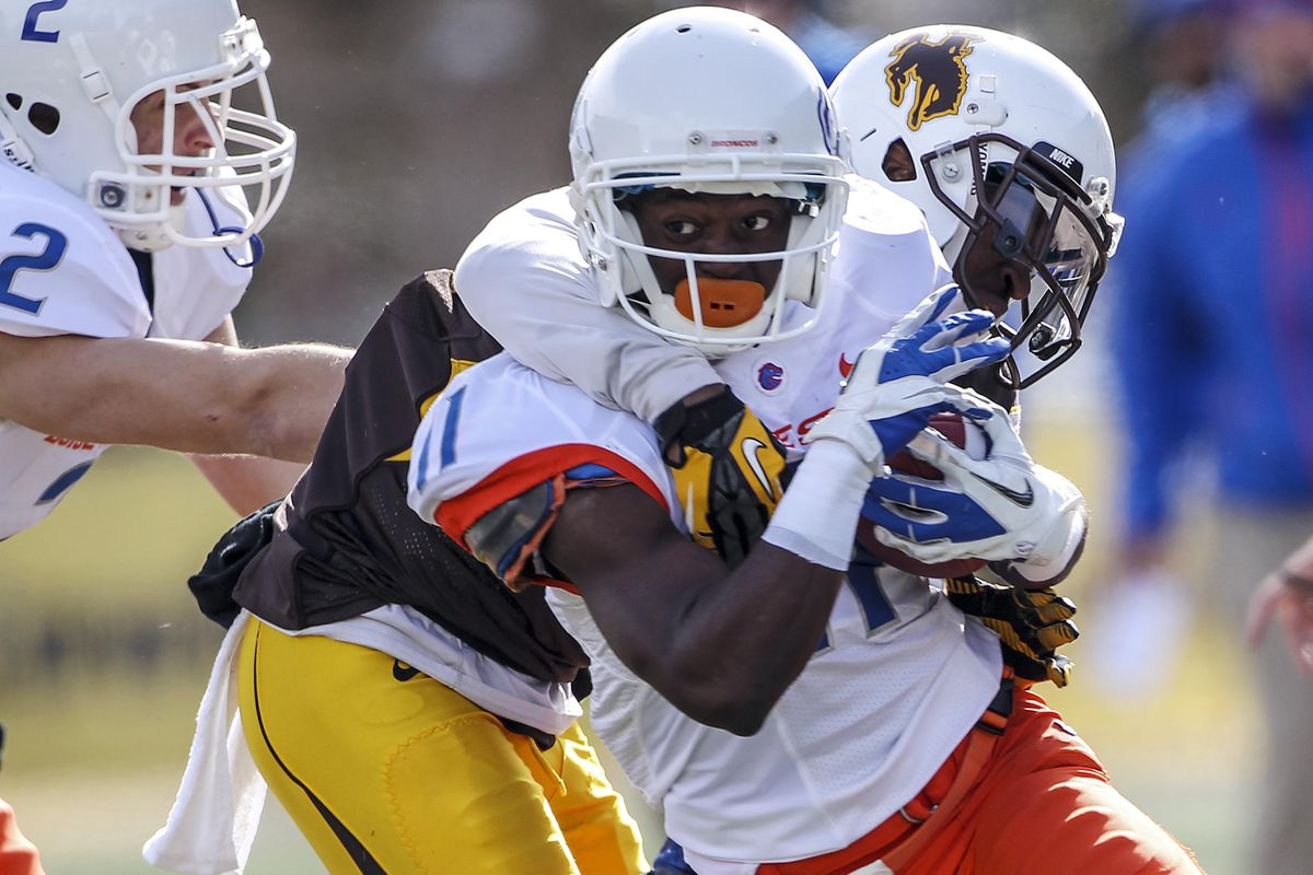 Oct 27, 2012; Laramie, WY, USA; Boise State Broncos wide receiver Shane Williams-Rhodes (11) is tackled by Wyoming Cowboys cornerback Blair Burns (20) during the first quarter at War Memorial Stadium. The Broncos beat the Cowboys 45-14. Mandatory Cre