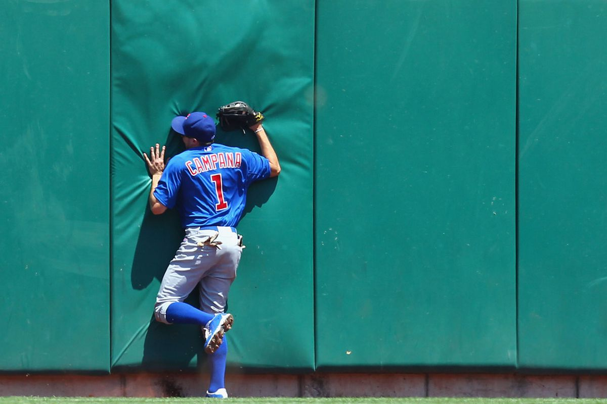 Tony Campana of the Chicago Cubs runs into the center field wall after catching a deep fly ball against the St. Louis Cardinals at Busch Stadium in St. Louis, Missouri.  (Photo by Dilip Vishwanat/Getty Images)