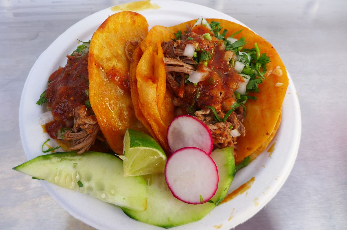 Two tacos filled with shredded beef, onions, salsa, and cilantro, with raw cucumbers on the side...