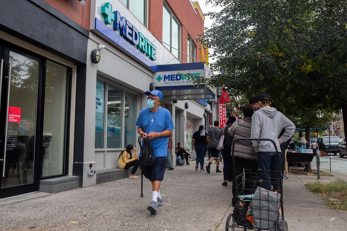 People wait in line outside an urgent care COVID testing site on Dyckman Street in Inwood, Oct. 6, 2021.