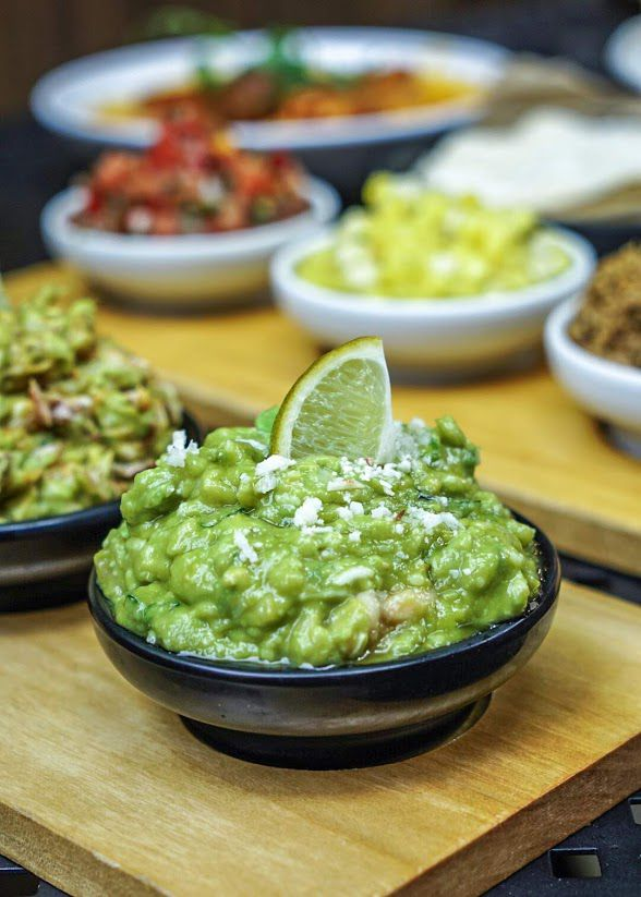 A close-up on a bowl of especially textured guacamole, with a lime wedge sticking out on top, on a wooden tray beside other dips