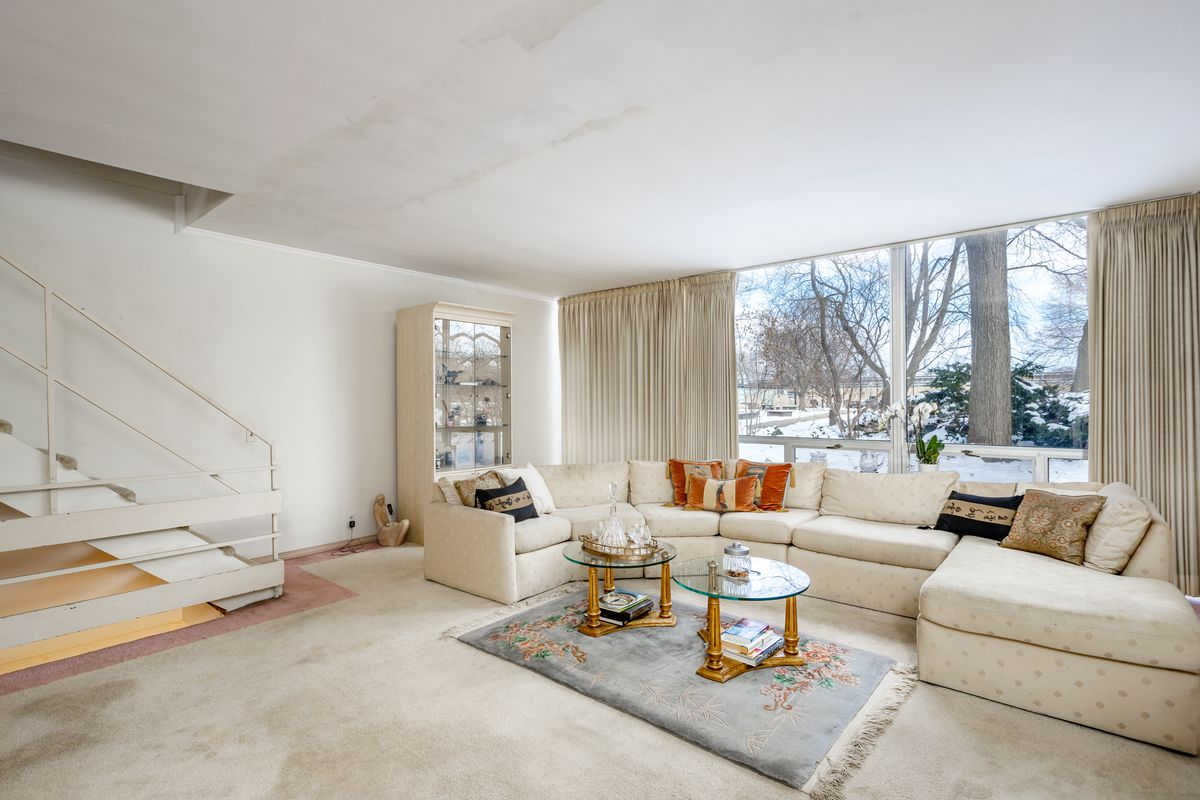 A carpeted room with a white sectional couch against floor-to-ceiling windows.