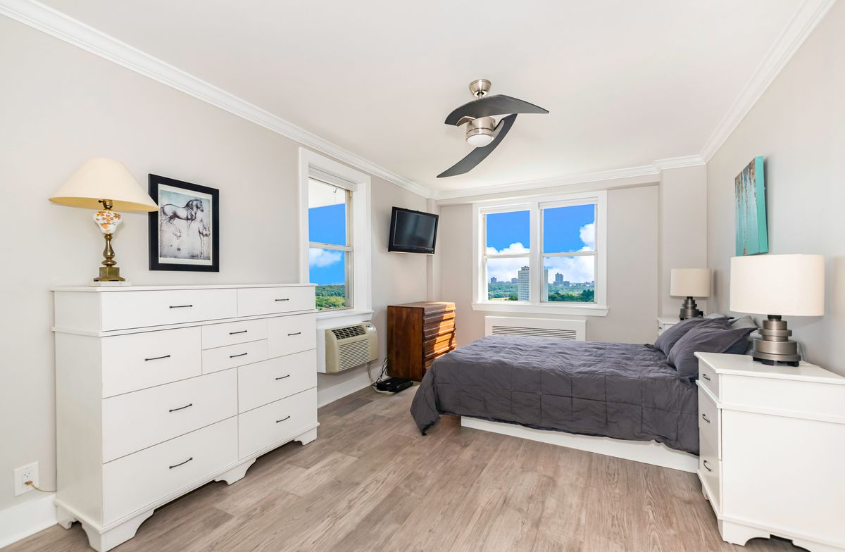 A bedroom with hardwood floors, grey walls, two windows, and a small bed.