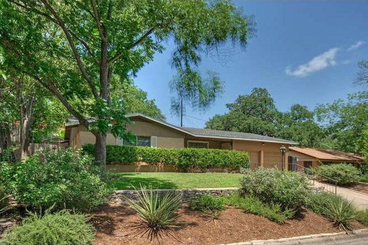 light-brown brick ranch style home with trees, hedges, and lawn in front