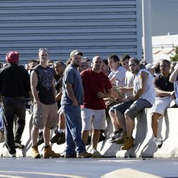 Workers wait outside a Boeing aircraft plant in Ridley Park, Pa. on Tuesday, Sept. 11, 2012 after part of the suburban Philadelphia facility was evacuated when a threatening note was found, according to a company spokesperson. Neither the company nor police divulged what was in the note or who left it.
